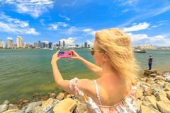 Woman photographs San Diego. Blonde tourist takes photo of San Diego By skyline by mobile phone with American flag cover. Female lifestyle takes pictures in royalty free stock photos