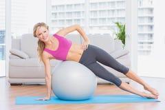 Blonde tuende Seitenplanke des netten Sitzes mit Übungsball Stockfoto