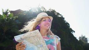 Blonde turístico de la chica joven en sombrero y con la mochila que mira el mapa del mundo en la playa almacen de video