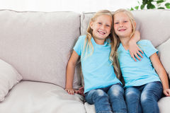 Blonde twins sitting on a couch Stock Images