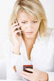 Blonde with two mobile phones. Surprised blonde with two mobile phones on a white background Stock Photo