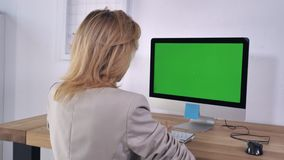 Businesswoman works on desktop. Blonde typing keyboard sitting at the working place with computer on the wooden desk display with green screen. Back view woman stock video footage