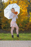 Blonde with an umbrella in autumn park Royalty Free Stock Photography