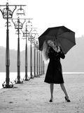 Blonde with umbrella on promenade Stock Photography