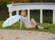 Blonde with umbrella is relaxing in autumn park Stock Photo