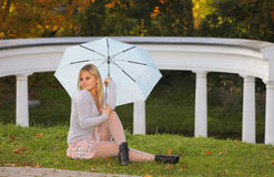 Blonde with umbrella is relaxing in autumn park Stock Photography