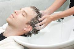 Blonde in un salone che ottiene lavato i suoi capelli con lo sha Fotografia Stock Libera da Diritti