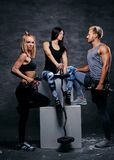Blonde und Brunettefrauen und athletischer ein Mann, der auf einem weißen b aufwirft Stockbilder