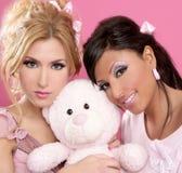 Blonde und Brunettemädchen umarmen einen rosafarbenen Teddybären Lizenzfreie Stockfotos