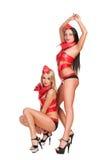 Blonde und Brunettetänzer in den roten Kostümen Stockfotografie