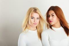 Blonde und dunkle Freunde zusammen Stockfotos