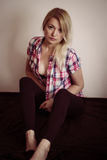 Blonde undressing. Blond woman sitting and taking off shirt royalty free stock photos