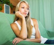 Blonde unglückliche Frau zu Hause Stockbilder