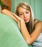 Blonde unglückliche Frau zu Hause Lizenzfreies Stockfoto