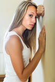 Blonde unhappy girl at home. Lonely long-haired blonde young woman depressed at home Royalty Free Stock Photos