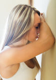Blonde unhappy woman at home. Crying lonely young woman feeling unhappy at home Stock Image