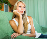 Blonde unhappy woman at home Stock Images
