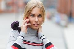 Blonde Unterhaltung am Telefon an der Straße Nahaufnahme Stockfoto