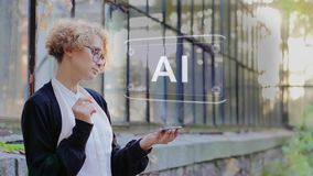 Blonde uses hologram AI. Curly young woman in glasses interacts with a hud hologram with text AI. Blonde girl in white and black clothes uses technology of the stock video