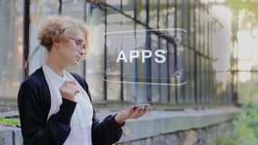 Blonde uses hologram APPS. Curly young woman in glasses interacts with a hud hologram with text APPS. Blonde girl in white and black clothes uses technology of stock video