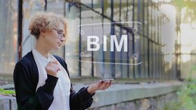 Blonde uses hologram BIM. Curly young woman in glasses interacts with a hud hologram with text BIM. Blonde girl in white and black clothes uses technology of the stock video