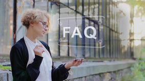 Blonde uses hologram FAQ. Curly young woman in glasses interacts with a hud hologram with text FAQ. Blonde girl in white and black clothes uses technology of the stock video