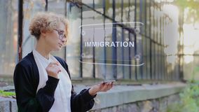 Blonde uses hologram Immigration. Curly young woman in glasses interacts with a hud hologram with text Immigration. Blonde girl in white and black clothes uses stock video footage