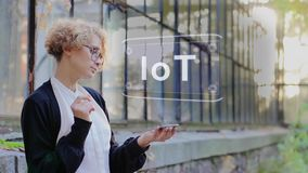 Blonde uses hologram IoT. Curly young woman in glasses interacts with a hud hologram with text IoT. Blonde girl in white and black clothes uses technology of the stock footage