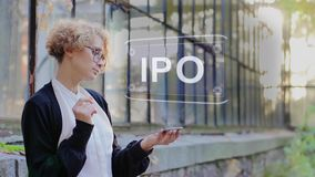 Blonde uses hologram IPO. Curly young woman in glasses interacts with a hud hologram with text IPO. Blonde girl in white and black clothes uses technology of the stock footage