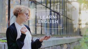 Blonde uses hologram Learn English. Curly young woman in glasses interacts with a hud hologram with text Learn English. Blonde girl in white and black clothes stock video