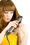 Blonde using hair straightener Stock Photography