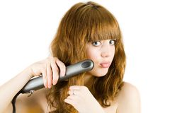 Blonde using hair straightener Royalty Free Stock Photos