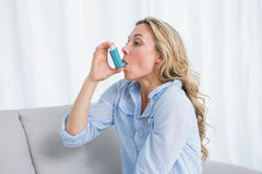 Blonde using her asthma inhaler on couch Stock Photos