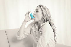 Blonde using her asthma inhaler on couch Royalty Free Stock Photography