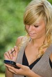 Blonde using pda. Beautiful young blonde using PDA outdoors Royalty Free Stock Images