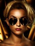 Blonde utilisant les lunettes de soleil élégantes photos stock