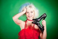 Blonde verrückte Mädchenholdingschuhe Lizenzfreie Stockfotografie