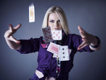 Blonde in violet on a grey scatters playing cards. Royalty Free Stock Photos