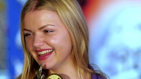 Blonde in violet jacket glad Cup victory by. Bowling. Blurred background. Close up stock footage