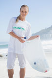 Blonde volunteer picking up trash on the beach Royalty Free Stock Photos