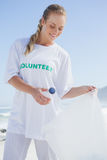 Blonde volunteer picking up trash on the beach Stock Image