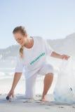 Blonde volunteer picking up trash on the beach Stock Image