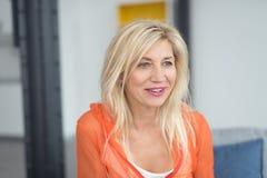 Blonde Volwassen Dame in Oranje Overhemd binnen het Bureau Royalty-vrije Stock Foto's