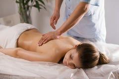 Blonde vorbildliche empfangende entspannende Massage der jungen Frau im Badekurortraum Stockbild
