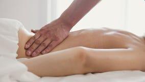 Blonde vorbildliche empfangende entspannende Massage der jungen Frau im Badekurortraum Stockfotos