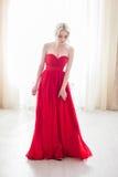 Blonde vorbildliche Frau der Schönheit, wenn rotes Kleid geglättet wird Stockfotos