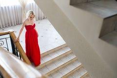 Blonde vorbildliche Frau der Schönheit, wenn rotes Kleid geglättet wird Stockfotografie