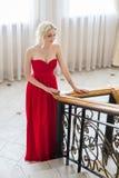 Blonde vorbildliche Frau der Schönheit, wenn rotes Kleid geglättet wird Stockbilder