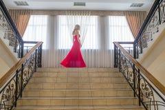 Blonde vorbildliche Frau der Schönheit, wenn rotes Kleid geglättet wird Stockbild