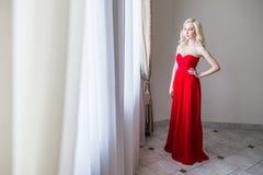Blonde vorbildliche Frau der Schönheit, wenn rotes Kleid geglättet wird Lizenzfreies Stockbild